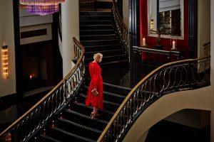 Frau auf der Lobbytreppe des Corinthia